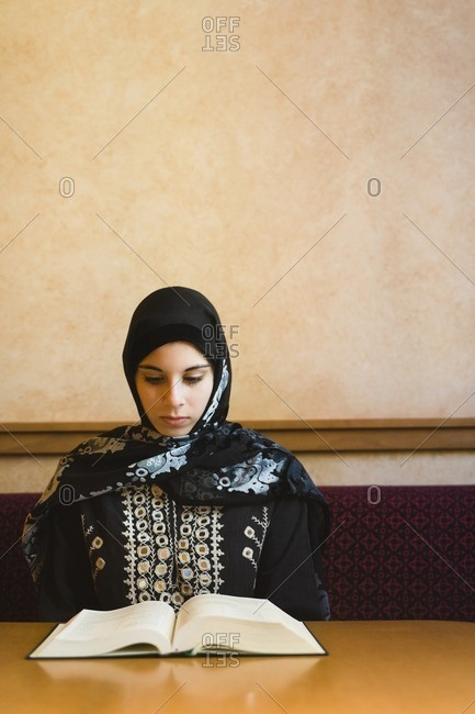 Middle Eastern teenager in headscarf reading book