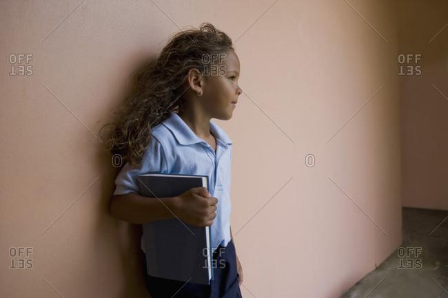 Hispanic school girl holding textbook