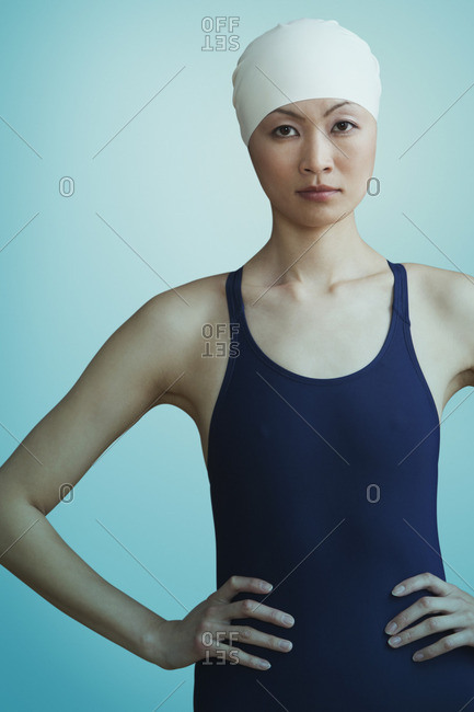 Serious Chinese woman in bathing suit and swimming cap