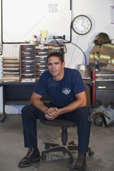 Hispanic fireman sitting in office