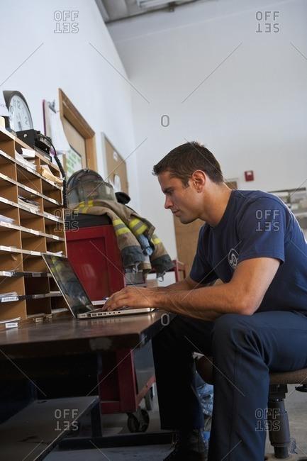 Hispanic fireman using laptop in office