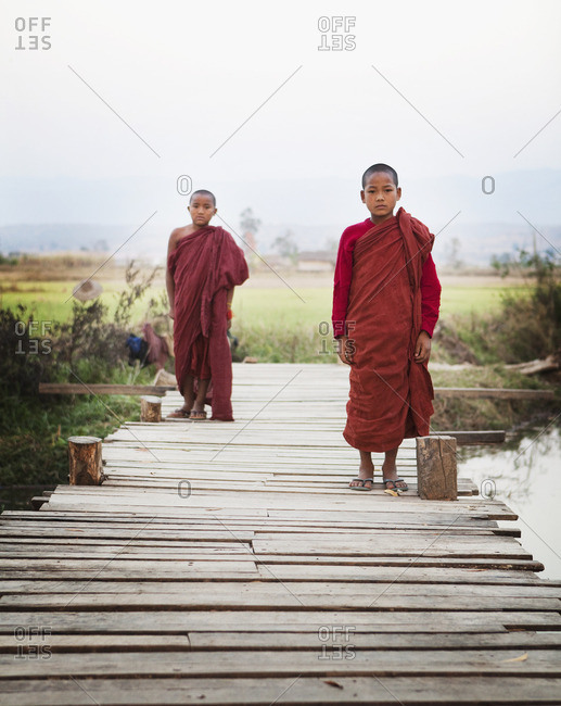 Asian boys in traditional robes walking on bridge