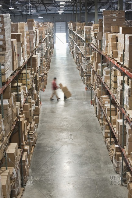 Hispanic man moving boxes with hand truck in warehouse