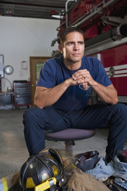 Hispanic fireman sitting with gear at feet