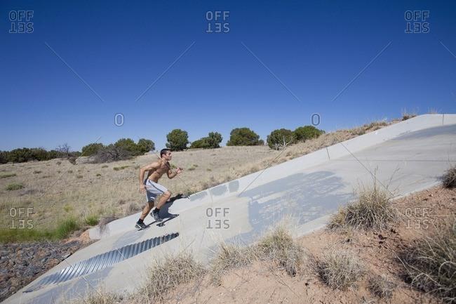 Hispanic man running up slope of culvert