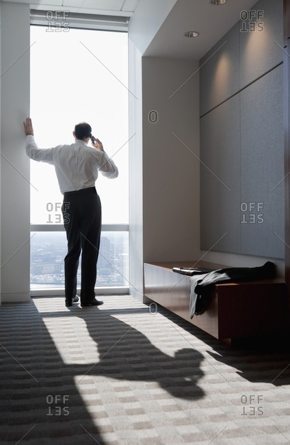 Mixed race businessman talking on cell phone at window