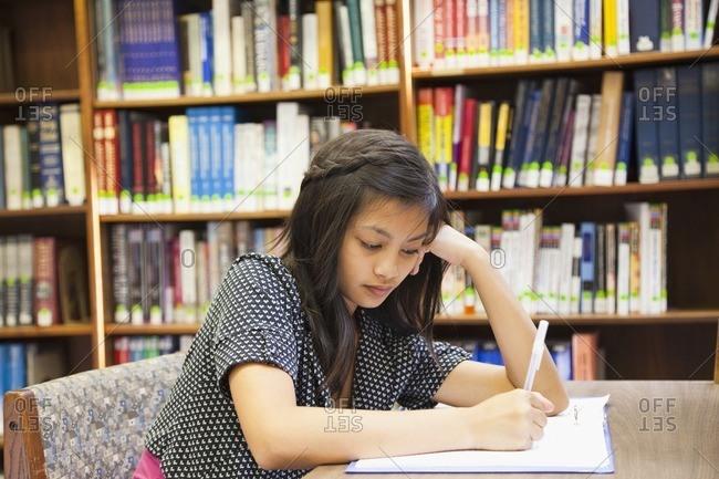 Asian girl doing homework in library