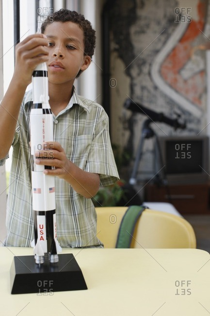 Mixed race boy building model rocket