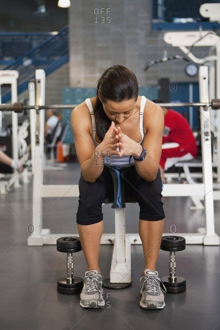 Mixed race woman sitting in health club