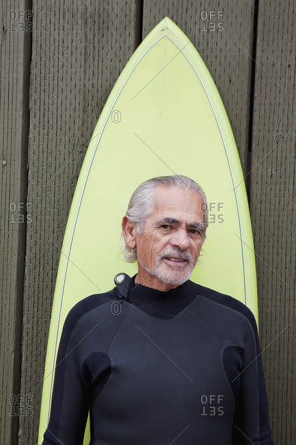 Senior Hispanic man with surfboard