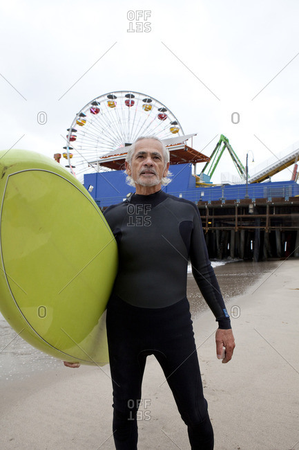 Senior Hispanic man carrying surfboard