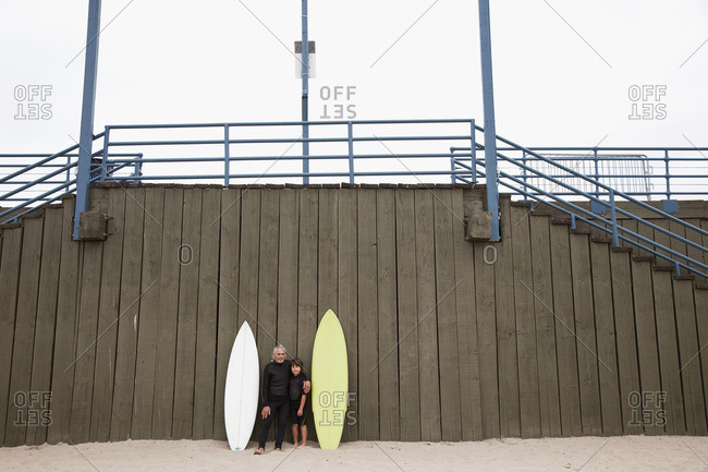 Hispanic grandfather and grandson in wet suits with surfboards