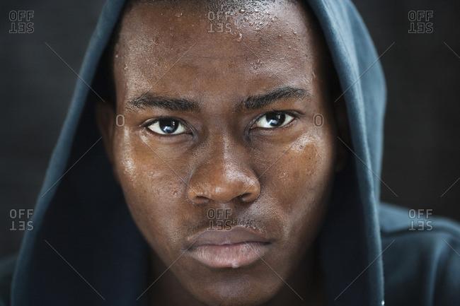 Sweating mixed race man in hoody