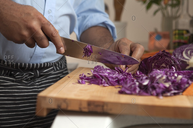 African American man cutting red cabbage