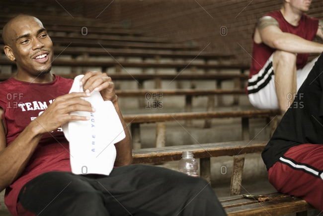 Basketball players sitting in bleachers