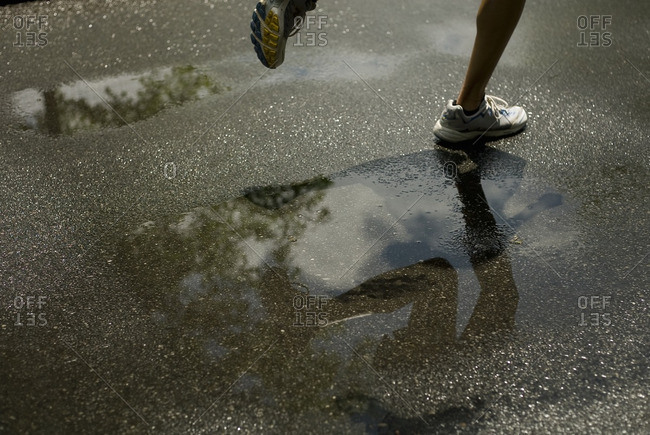 Woman running through puddle
