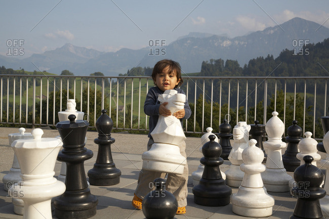 Mixed race boy playing with large chess pieces