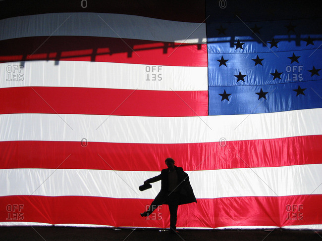 Silhouette of man behind American flag