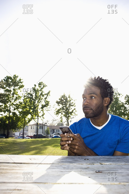 African American man text messaging outdoors