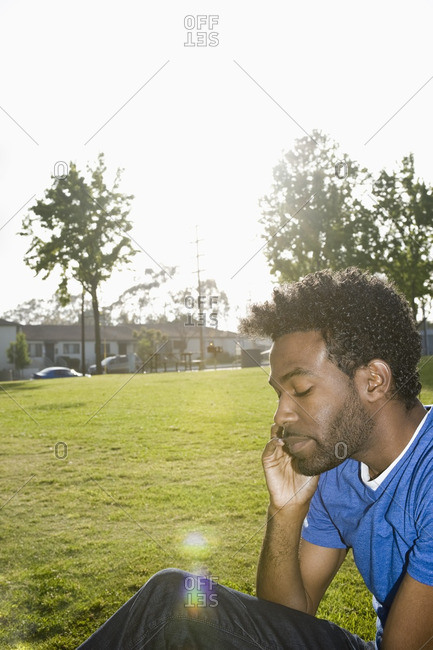 African American man sitting outdoors using cell phone