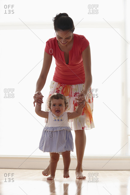 Hispanic mother teaching daughter to walk