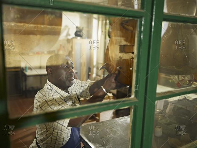 Black lute maker in workshop