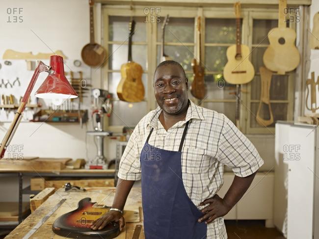 Black craftsman in guitar workshop