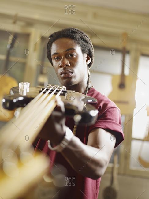 African American craftsman looking at guitar in workshop
