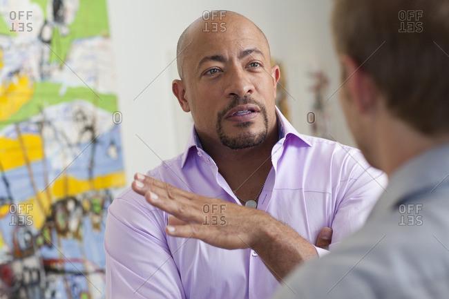 Businessmen talking in art gallery