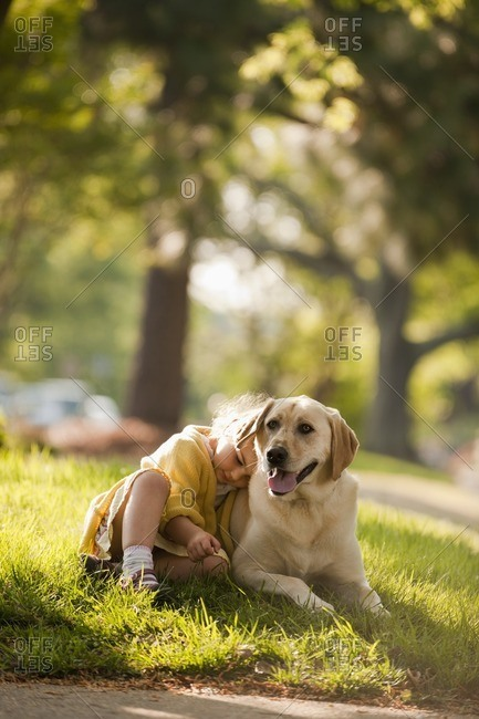 Caucasian girl playing with dog in yard