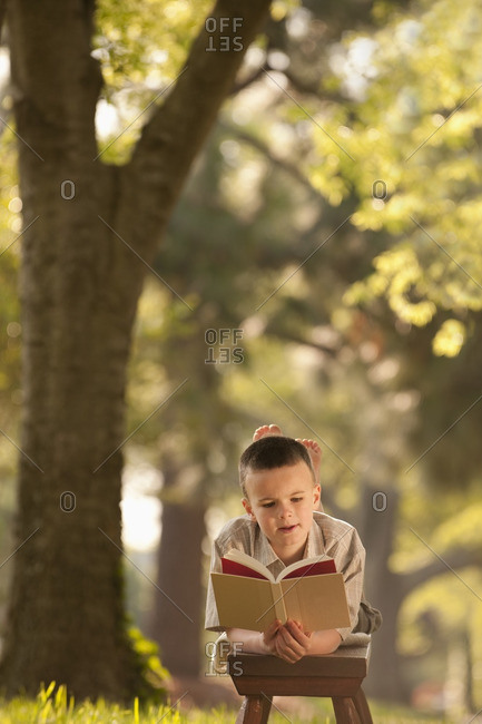 Caucasian boy reading book in yard