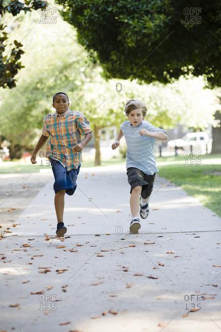 Boys running on sidewalk