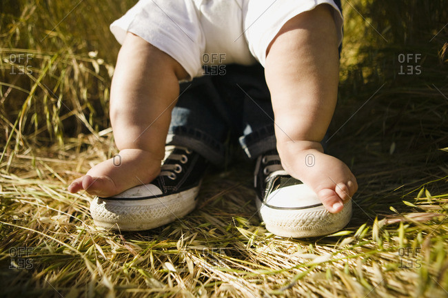 Baby's feet on top of father's feet