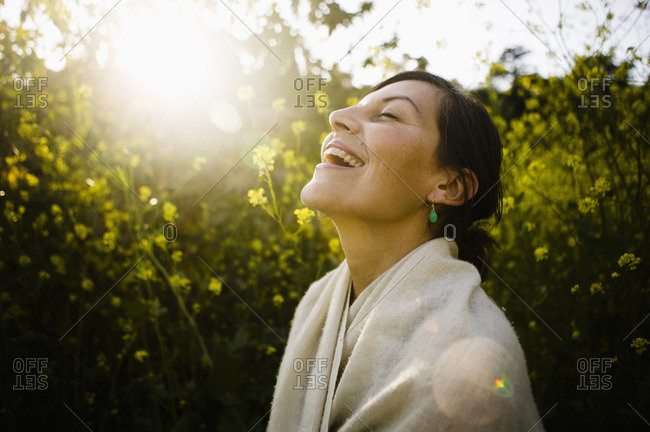 Laughing mixed race woman with eyes closed in field