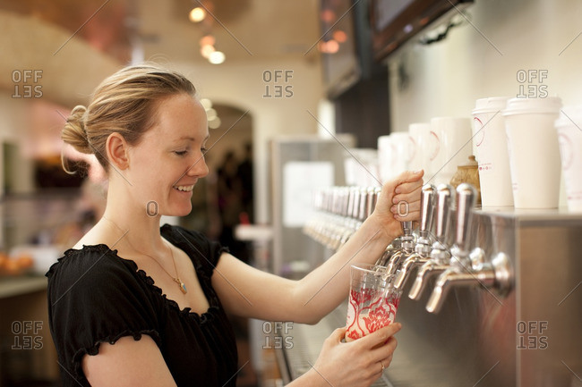Smiling Caucasian woman filling cup from dispenser