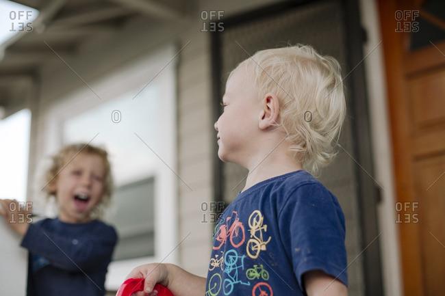 Two children making mischief on the porch