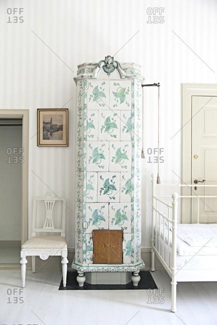 Tomelilla, Sweden - July 6, 2013: Antique tiled stove in bedroom at Kronovall Castle