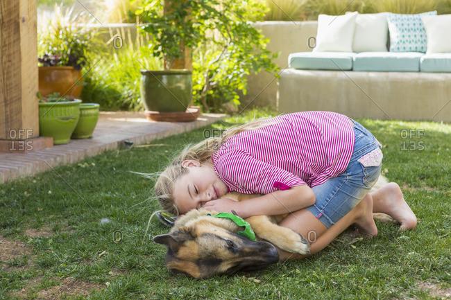 Girl hugging dog in a yard