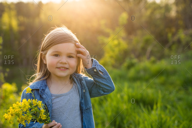 Little girl holding a bunch of yellow flowers at sunset