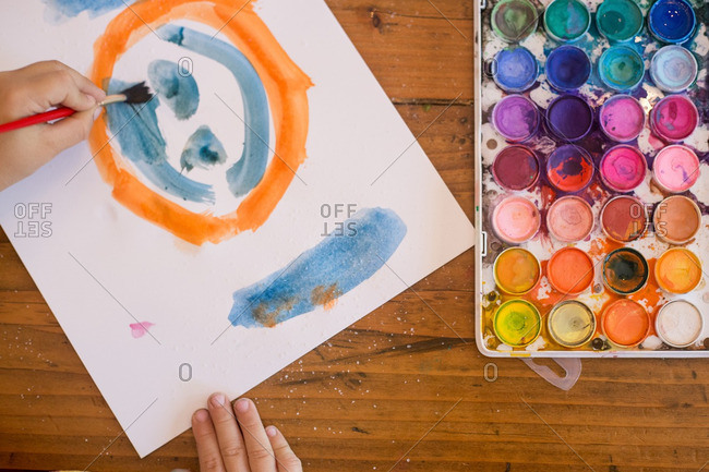 Child painting orange and blue smiley face with watercolors on table
