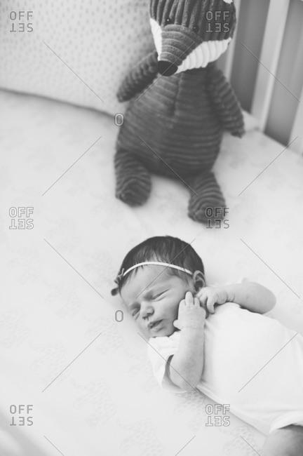 Baby sleeping in crib by doll