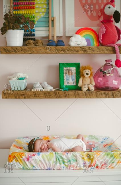 Baby asleep under shelves