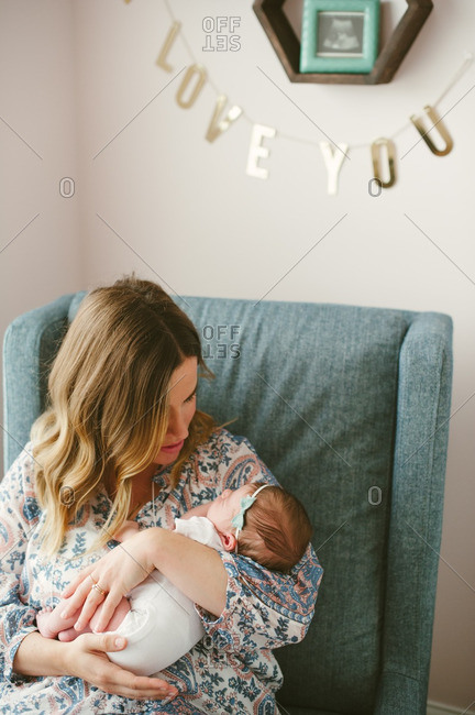 Mom holding newborn in chair