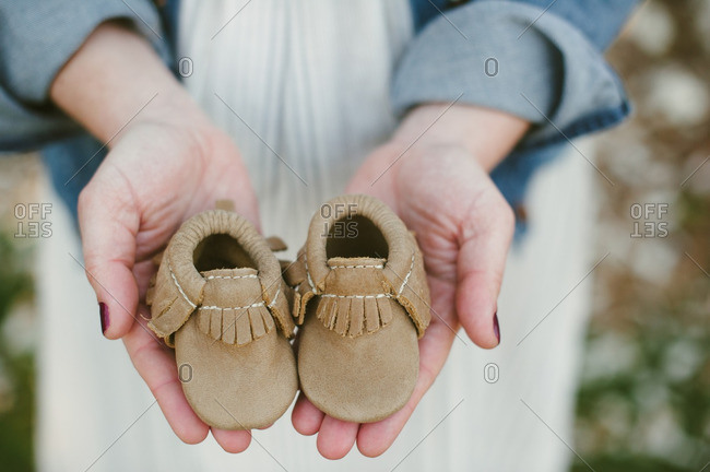 Woman holding infant moccasins