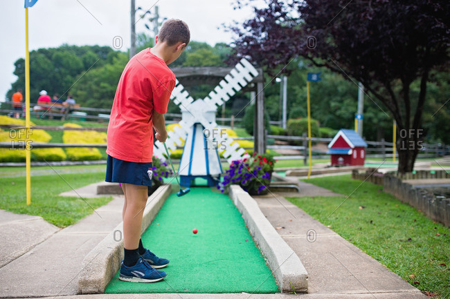 Boy playing mini-golf