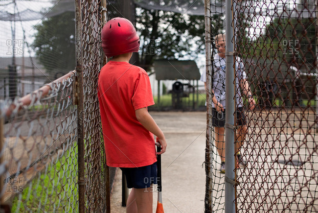 Boy leaning on fence during baseball practice