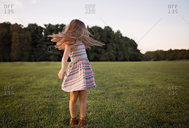 Little girl twirling her hair in a country field