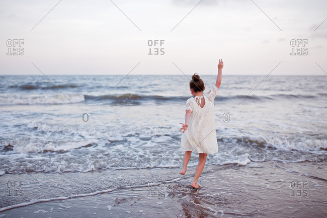 Girl jumping in the waves in the ocean