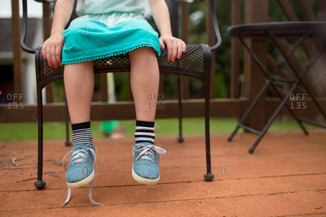Little girl sitting on deck chair with untied shoe