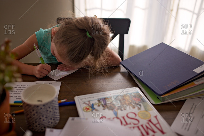Little girl doing homework at dining room table